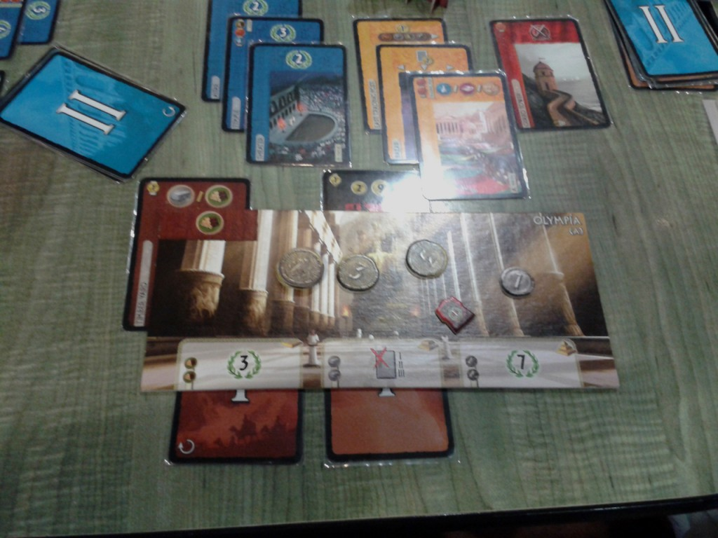 An up-close view of the Olympia wonder board. As a player builds the wonder in stages, cards are placed under the bottom edge of the board, indicating they were used to build the wonder instead of other buildings. The top left corner of the wonder is where production cards stack up, indicating the resources available. Above the board are the buildings build (so far) in this city. Pardon the glare - the cards are sleeved and the lighting in the deli wasn't the best.