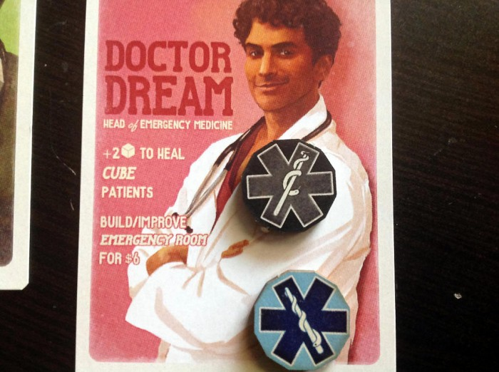 Doctor Dream, looking a lot like Perry Cox from Scrubs. He has his two Medical Action markers to help keep track of the things he does; one is turned over to indicate he's already used one this turn. He is apparently SO dreamy, that he gets to draw bonus cubes when healing any type of patient.