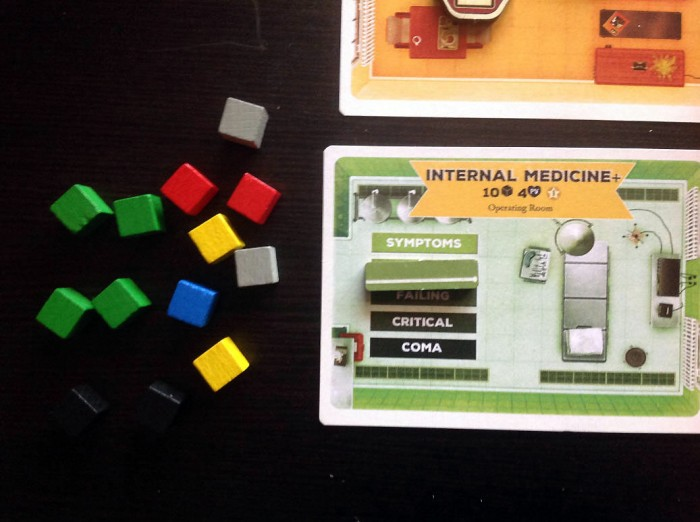 This is an Improved Operating Room, so it lets you draw ten cubes to try to heal. The extra cube is from a bonus training counter on the healing doctor (in this case, it's not Doctor Chang). The patient is at illness level 2 (you use an EKG bar to mark their level of illness here), and drawing four green cubes means healing four levels – so this patient is cured!
